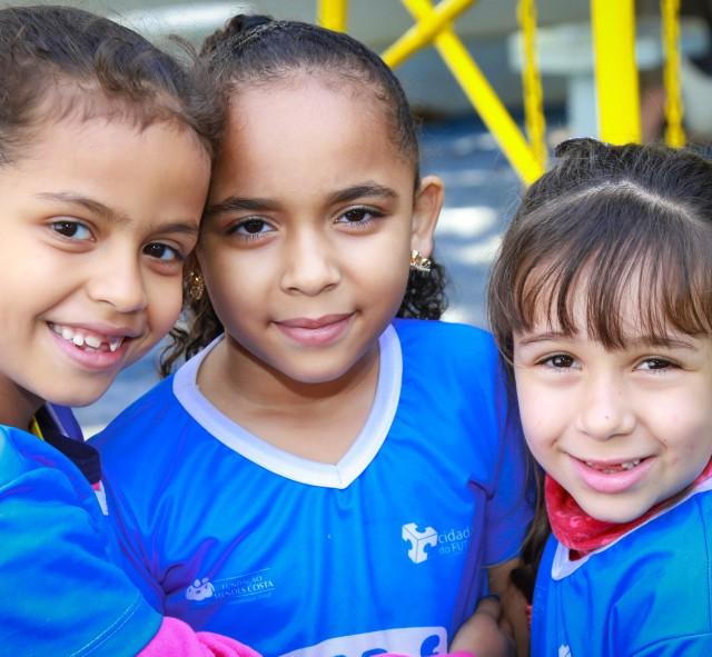 Fotografia com três crianças se abrançando e sorrindo